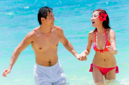 An attractive Asian couple in the sea playing around Stock Photo - 4801303