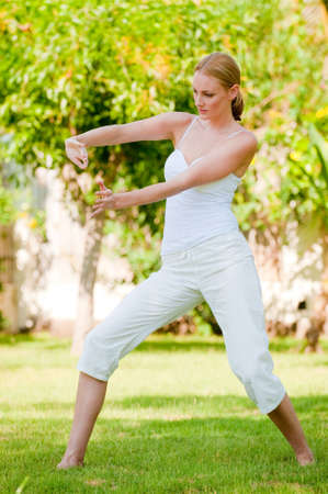 A slim tall woman doing tai chi outside photo