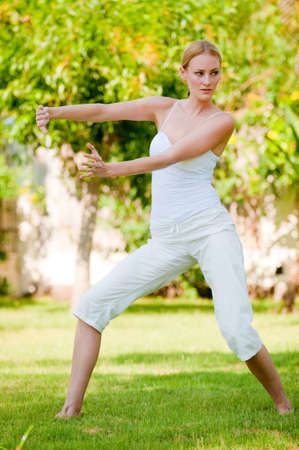 A slim tall woman doing tai chi outside photo