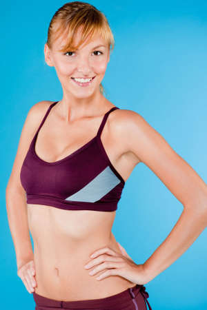 An attractive toned woman posing in purple sports attire on blue background photo