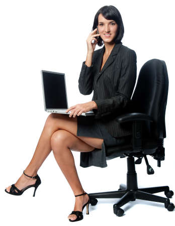 skirt suit: An attractive businesswoman sitting down with a laptop and using a phone on white background Stock Photo