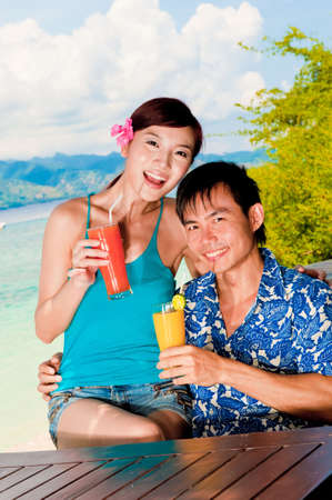 sipping: An attractive couple sipping on juices outside on tropical island