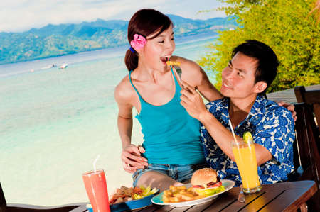 An attractive couple sipping on juices outside on tropical island