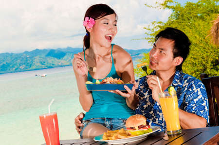 An attractive couple eating lunch outside on tropical island photo