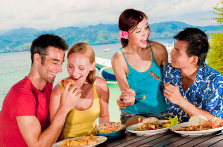 An attractive group eating lunch outside on tropical island photo