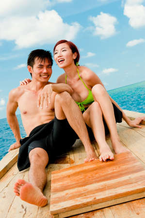 A young couple sitting on a wooden boat photo