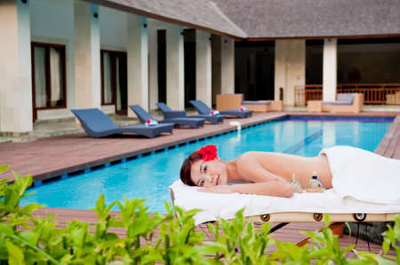 A young Chinese woman lying on a massage table outside of a luxury villa photo