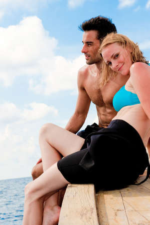 An attractive couple sitting on a wooden boat in the ocean Stock Photo - 4986533