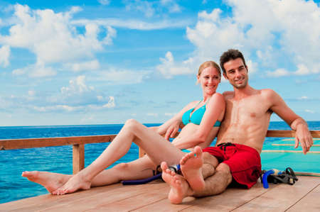 An attractive couple sitting on a wooden boat in the ocean Stock Photo