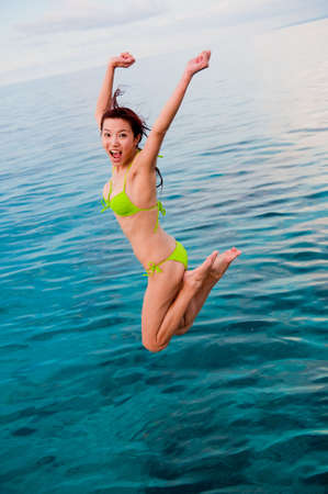 An attractive Chinese woman jumping into the sea Stock Photo