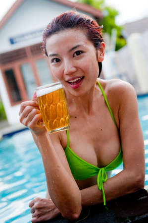 A young attractive Chinese woman drinking a beer in the pool photo