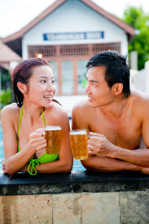 Asian Couple Drinking Beer in Pool Stock Photo - 4986520