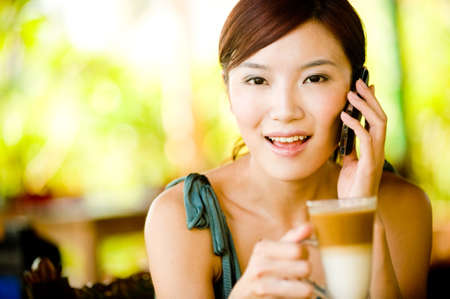 handphone: A young woman enjoying breakfast whilst on vacation Stock Photo