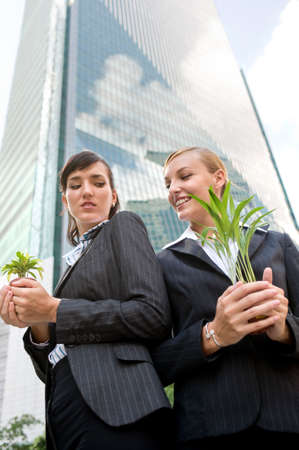 unsatisfied: Two competitive businesswomen cupping their plants in their hands Stock Photo