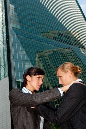 animosity: Two attractive businesswomen fighting against city backdrop