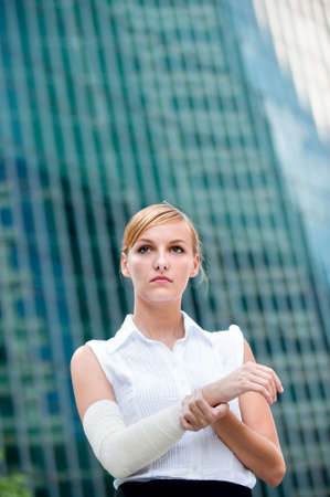 A young businesswoman holds her injured arm against city backdrop