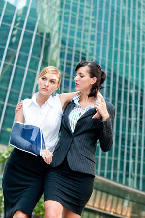 broken arm: A young businesswoman with injured arm and bandaids walking and supported by a friend Stock Photo