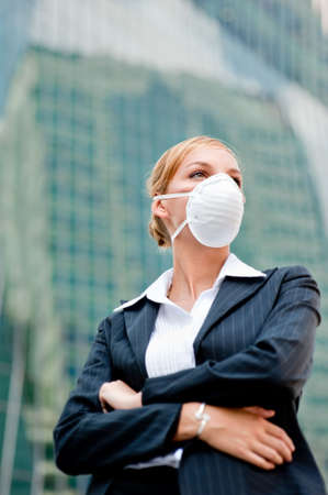 flu: A young businesswoman wearing a health mask against city backdrop