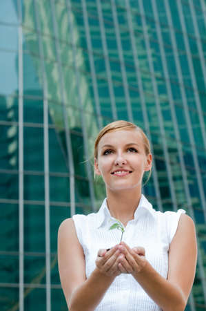 An attractive businesswoman cupping a plant in her hands against city backdrop photo