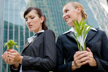 envious: Two competitive businesswomen cupping their plants in their hands Stock Photo