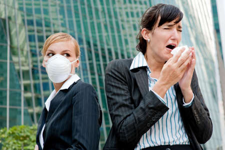 paranoia: A businesswoman sneezing as another with health mask on stares at her Stock Photo