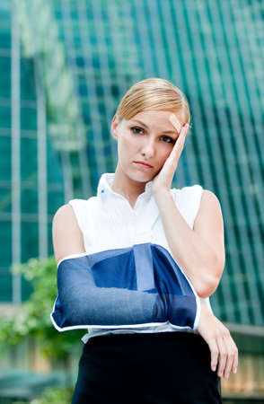 A young businesswoman with injured arm and bandage standing in the city Stock Photo