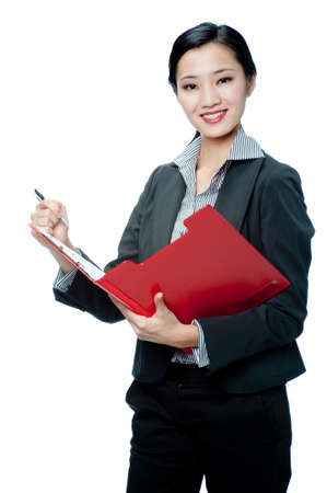 An attractive Asian businesswoman in a suit writing in a red clipboard on white background photo