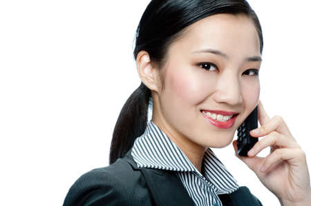 An attractive Asian businesswoman talking on phone against white background Stock Photo - 5056082