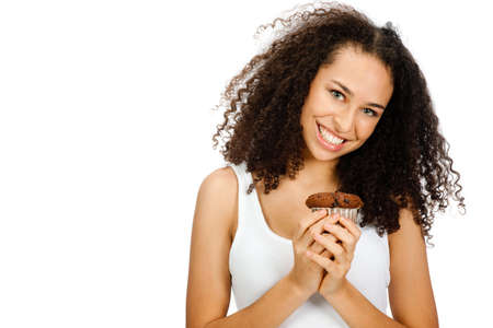 A young and attractive teenager holding a cupcake in her hands against white background photo
