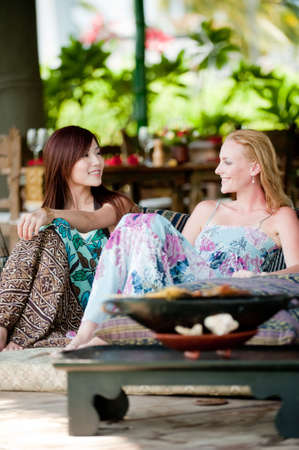 Two young attractive women having lunch and drinks on vacation photo