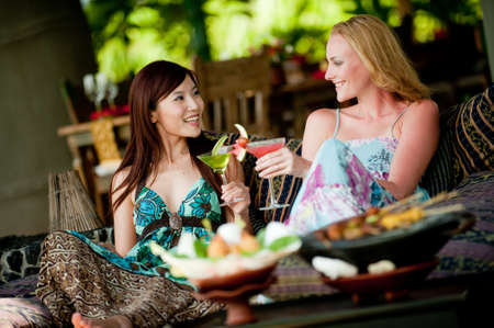 sharing food: Two young attractive women having lunch and drinks on vacation
