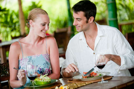 A good-looking couple having meal with wine photo