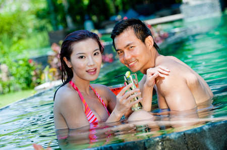 An attractive Chinese woman and man in swimming pool with cocktails photo