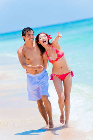 An attractive Asian couple walking along the beach at the edge of the water Stock Photo - 5155616