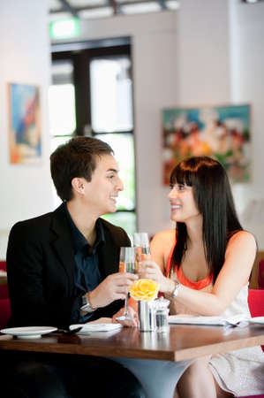 An attractive young couple toasting with white wine in a restaurant Stock Photo - 5179594
