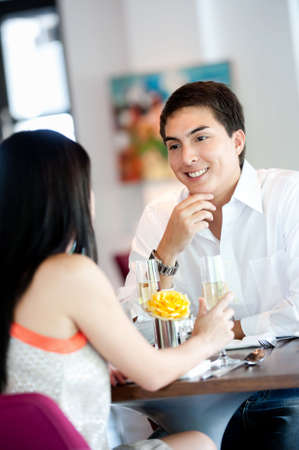 An attractive young man talking to his partner at a restaurant Stock Photo - 5179601