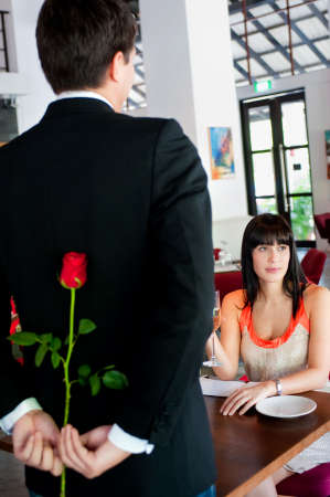 A young and attractive man holding a rose behind his back to surprise his partner in a restaurant Stock Photo - 5179597