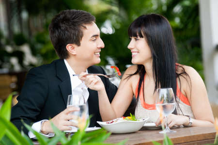 An attractive young couple shares a salad at an outdoor restaurant Stock Photo - 5179596