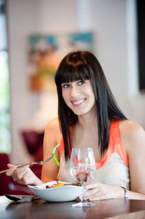 A young and attractive woman eating a salad in an indoor restaurant Stock Photo - 5179617