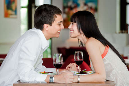 A young and attractive couple holding hands and about to kiss over their dinner in an indoor restaurant Stock Photo - 5179616