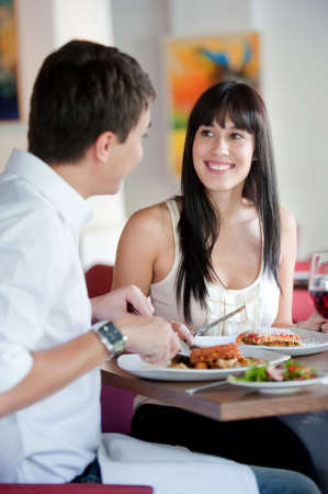 A young and attractive woman dining with her partner in an indoor restaurant Stock Photo - 5179611