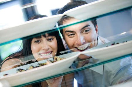 A young and attractive couple looking at dishes arranged behind a counter Stock Photo - 5179598