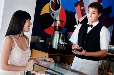 A young and attractive waiter taking an order from a customer in an indoor restaurant Stock Photo - 5179612