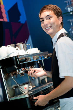 A young and attractive barista making a coffee in an indoor restaurant photo