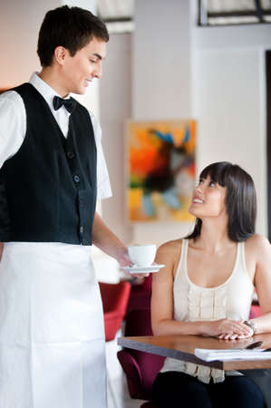 A young and attractive waiter serving coffee to a customer in an indoor restaurant Stock Photo - 5179604