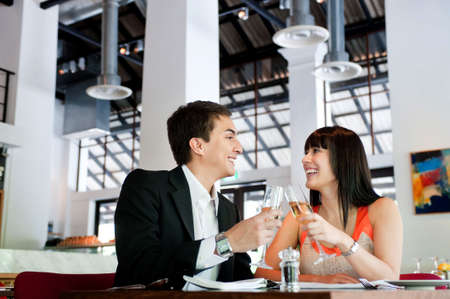 An attractive young couple toasting with white wine in a restaurant Stock Photo - 5204052
