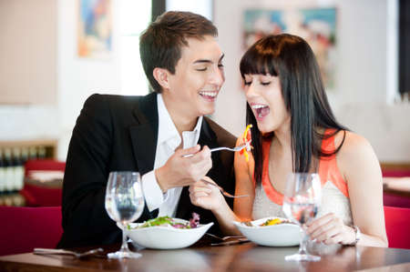 A young and attractive man feeds his girlfriend while they dine in a restaurant