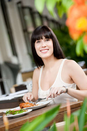 A young and attractive woman having a meal in an outdoor restaurant
