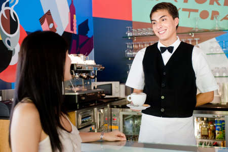 A young and attractive waiter serving coffee to a customer in an indoor restaurant photo