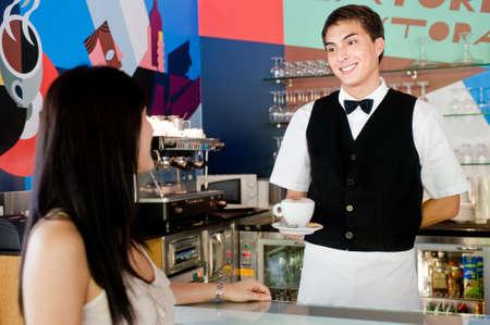 camarero: Un joven y atractivo camarero sirviendo caf� a un cliente en un restaurante de interior